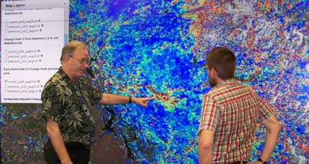 Bill Hargrove, left, and ORNL research scientist Forrest Hoffman use a ForWarn map to examine growing impacts of the Yosemite Rim Fire. Photo by Jitendra Kumar, ORNL.