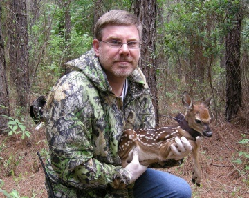 Forest Service Research Wildlife Biologist John Kilgo with a fawn