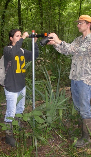Student intern Andreza Martins (l.) and SRS biological science technician Carl Smith (r.) focusing video camera on pondberry plot to record animal visits. Photo by Collin Tidwell.