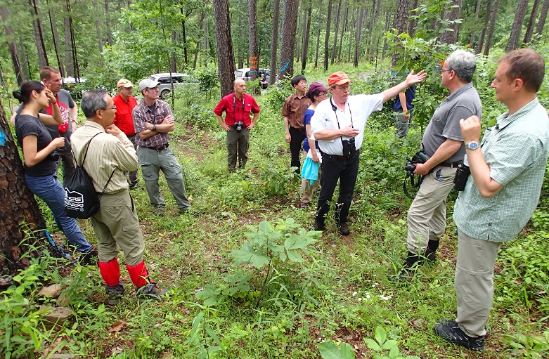 Jim Guldin (arm raised) explains aspects of shortleaf pine silviculture on the Ouachita National Forest to post-workshop tour participants. Photo by Don Bragg.