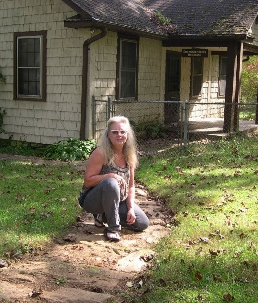 Linda Bentz kneeling on one of the flagstone walkways she uncovered, one of a web of walkways that connect the buildings on the historic campus of the Bent Creek Experimental Forest. Photo by U.S. Forest Service.