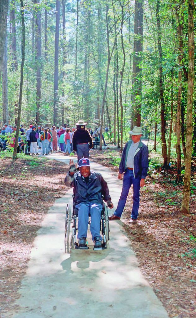 A man in a wheelchair on the paved interpretive trail at Stephen F. Austin Experimental Forest