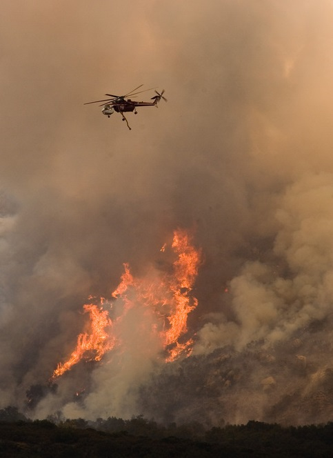 A helicopters drops water and retardant to stop a wildfire in California from advancing. Photo by Andrea Booher/FEMA