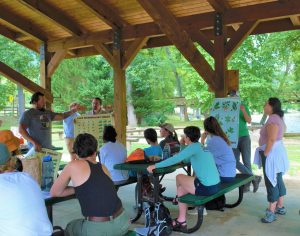 A group gathers under a picnic shelter as the module is presented