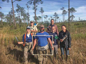 The sampling team - six people - stand in prairie with pine trees behind them