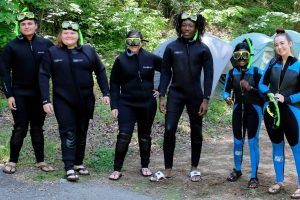 A group of young people, wearing wet suits, stands in a line smiling