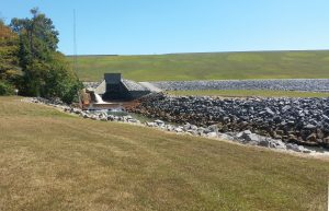 a small stream disappears as it travels under the berm of an earthen dam