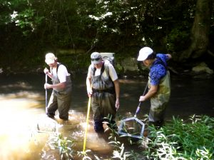 three people stand in a stream with nets and gear