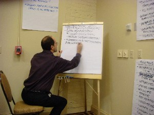 photo: Kier Klepzig writing on a flipchart with other pages pasted on the walls