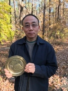 Qinfeng Guo holding his award medal