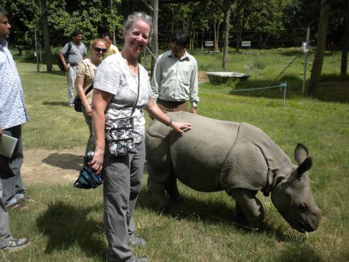 Susie Adams standing next to a baby rhinoceros